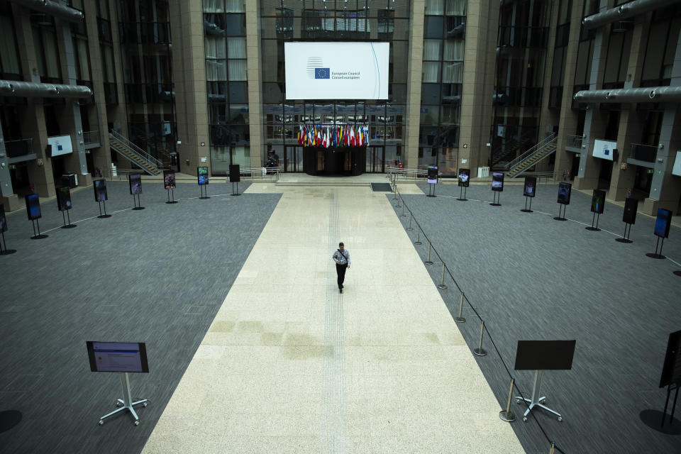 A man walks in the empty atrium, usually full of tables for journalists to work during EU summits, at the European Council building in Brussels, Thursday, July 16, 2020. On Friday, July 17, 2020, leaders from the 27 European Union nations will meet face-to-face to try to carve up a potential package of 1.85 trillion euros among themselves. Due to coronavirus concerns, Friday's summit will be held in a larger-than-usual meeting room to meet social distancing requirements, the media will be kept to a minimum and there will be no group photo of the leaders. (AP Photo/Francisco Seco)