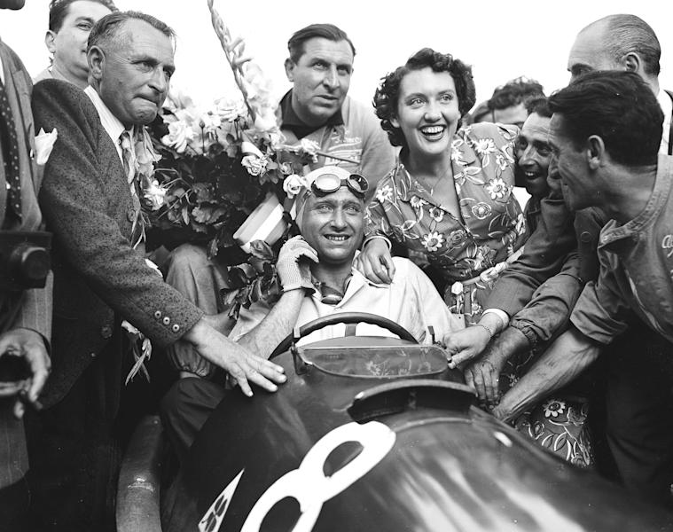 FILE - In this July 2, 1957, file photo, Juan Manuel Fangio, of Argentina, is surrounded by a crowd after winning the Grand Prix of Europe at Rheims, France. Fangio cheerily muscled his way to five championships in an era when cars and race courses had to be tamed through brute strength and driven with the foolhardy courage necessary to cheat death to get to the checkered flag. More than 60 years since Fangio was conquering race tracks in the 1950s, Lewis Hamilton can match Fangio's five championships this weekend at the Mexican Grand Prix. (AP Photo/File)