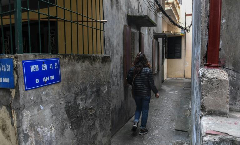 Nga walks toward the lane where her daughter was was molested in a residential quarter of Hanoi