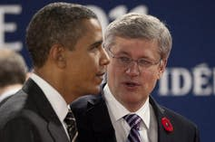 Stephen Harper talks to Barack Obama.