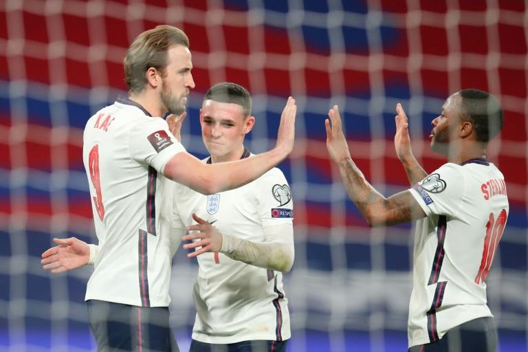 England striker Harry Kane (left) celebrates after scoring a penalty against Poland