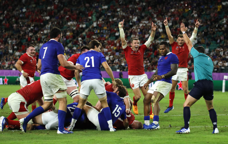 Wales players celebrate after Ross Moriarty scores a try during the Rugby World Cup quarterfinal match against France at Oita Stadium in Oita, Japan, Sunday, Oct. 20, 2019. (AP Photo/Christophe Ena)