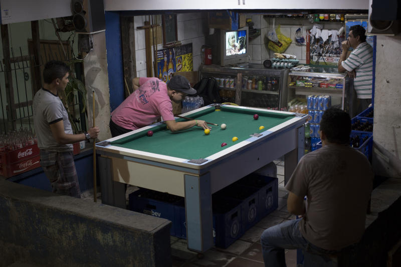 """Men shoot pool as others watch the final episode of soap opera Avenida Brasil in the Dona Marta slum in Rio de Janeiro, Brazil, Friday, Oct. 19, 2012. """"Telenovelas,"""" prime-time soap operas with average runs of 200 episodes, are hugely popular in Brazil, where the plot lines often become front page news and where discussions of the heroes and villains are a major topic of conversation. (AP Photo/Felipe Dana)"""
