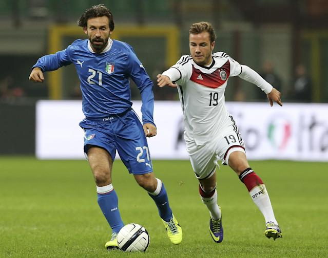 Italy midfielder Andrea Pirlo, left, challenges for the ball with Germany midfielder Mario Gotze during a friendly soccer match between Italy and Germany at the San Siro stadium in Milan, Italy, Friday, Nov. 15, 2013. (AP Photo/Antonio Calanni)