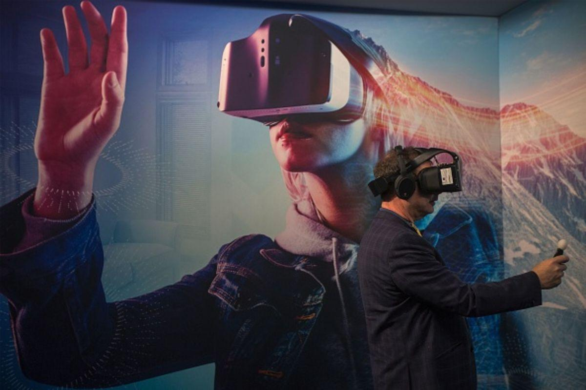 A man wearing a VR headset experiments with a merged reality experience using Project Alloy at the Intel exhibit during the 2017 Consumer Electronic Show (CES) in Las Vegas, Nevada, January 6, 2017. / AFP / DAVID MCNEW (Photo credit should read DAVID MCNEW/AFP/Getty Images)