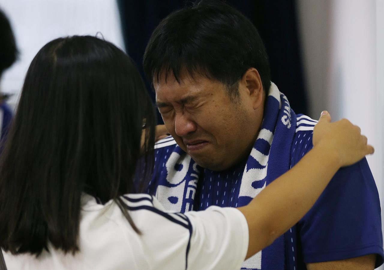 <p>A Japanese fan cries during the broadcast of the FIFA World Cup soccer match. REUTERS/Paulo Whitaker </p>