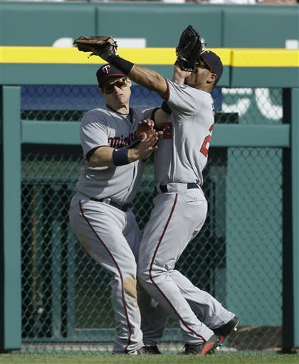 Minnesota Twins center fielder Wilkin Ramirez, right, and left fielder Josh Willingham collide after chasing a fly ball hit by Detroit Tigers' Omar Infante during the sixth inning of a baseball game in Detroit, Saturday, May 25, 2013. Ramirez held on to the ball for the out. (AP Photo/Carlos Osorio)