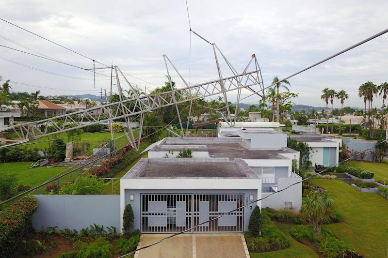 A power line tower, downed by Hurricane Maria, is seen resting on top of a house in San Juan, Puerto Rico, on Nov. 7. (RICARDO ARDUENGO via Getty Images)