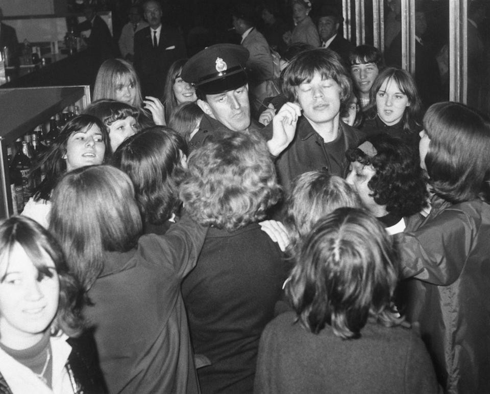 <p>Police help escort Mick Jagger as he's swarmed by fans at the airport in London.</p>
