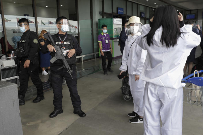 A policeman reminds passengers to wear their face shields properly at Manila's International Airport, Philippines, Monday, Jan. 18, 2021. Coronavirus infections in the Philippines have surged past 500,000 in a new bleak milestone with the government facing criticisms for failing to immediately launch a vaccination program amid a global scramble for COVID-19 vaccines. (AP Photo/Aaron Favila)