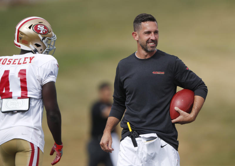 FILE - In this Aug. 16, 2019, file photo, San Francisco 49ers head coach Kyle Shanahan, right, jokes with cornerback Emmanuel Moseley during a combined NFL football training camp with the Denver Broncos at the Broncos' headquarters in Englewood, Colo. Commissioner Roger Goodell told the 32 NFL clubs on Thursday, June 4, 2020, that coaching staffs are allowed to return to team facilities starting Friday. (AP Photo/David Zalubowski, File)