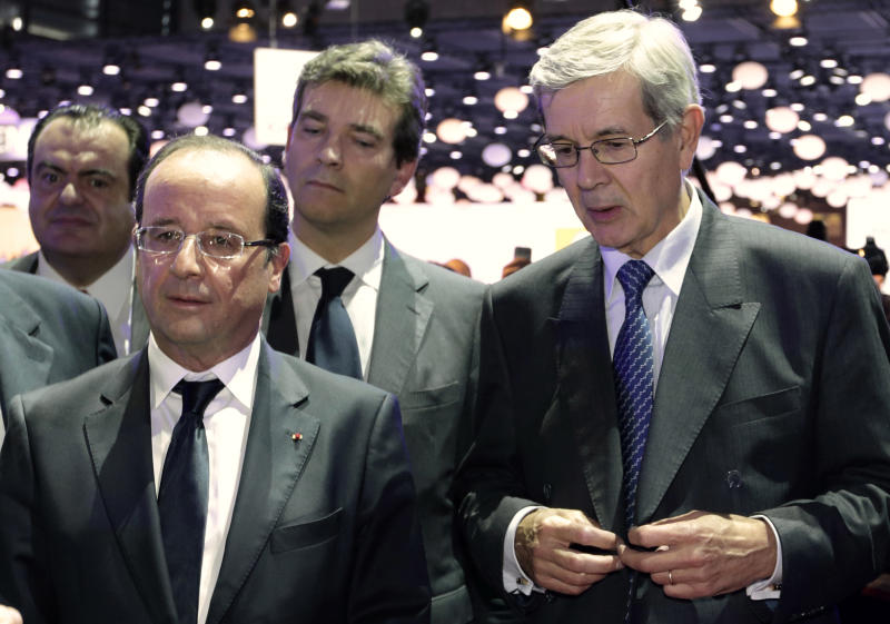 France's President, Francois Hollande, left, and Chief Executive of French carmaker PSA Peugeot Citroen Philippe Varin, right, are seen on the eve of the opening of the Paris Auto Show, Friday, Sept. 28, 2012. The Paris Auto Show will open its gates to the public from Sept. 29 to Oct. 14. (AP Photo/Philippe Wojazer, Pool)