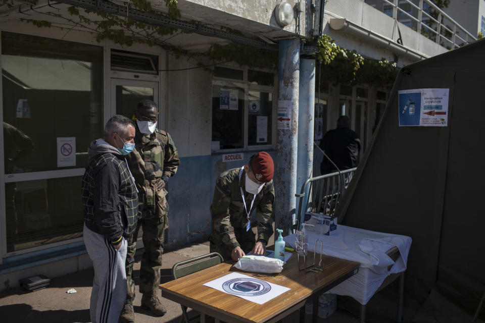 A French soldier receives people at a vaccination center set up at the Laveran Military Hospital in Marseille, southern France, Wednesday, April 7, 2021. Seven military hospitals also opened vaccination centers on Tuesday, operated by military and civilian staff, in an effort to inject up to 50,000 doses per week, the defense ministry said. (AP Photo/Daniel Cole)