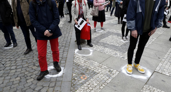 People try to maintain social distance as they gather for a demonstration in Prague, Czech Republic, Thursday, April 29, 2021. Thousands of Czechs have rallied in the capital against President Milos Zeman, accusing him of treason for his pro-Russian stance over the alleged participance of Russian spies in a Czech huge ammunition explosion. (AP Photo/Petr David Josek)