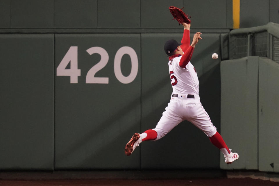 Boston Red Sox center fielder Enrique Hernandez leaps but can't make the play on an RBI double by Detroit Tigers' Robbie Grossman during the fifth inning of a baseball game at Fenway Park, Tuesday, May 4, 2021, in Boston. (AP Photo/Charles Krupa)