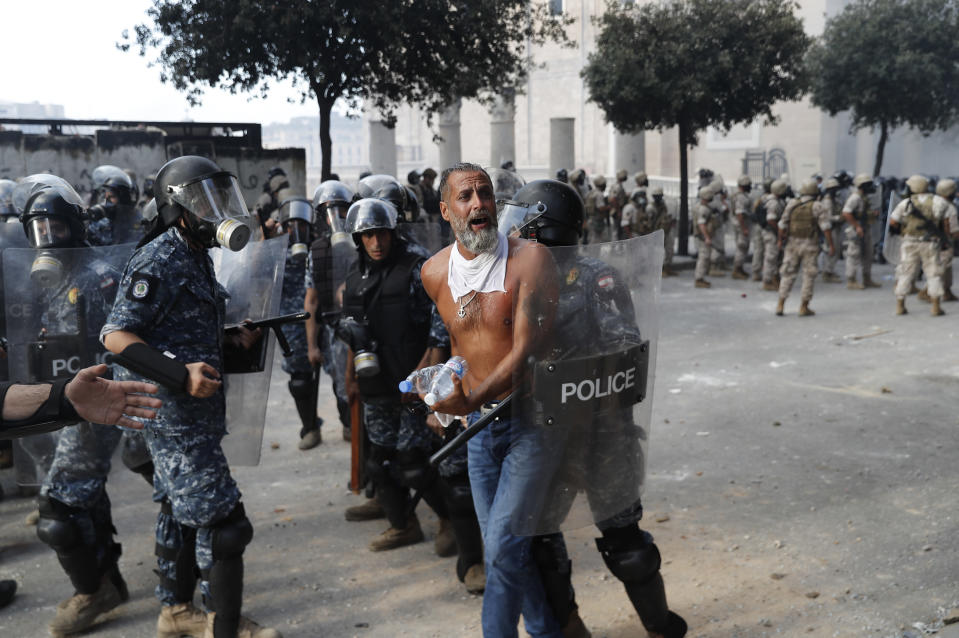 Lebanese riot police arrest an anti-government protester, who was trying to reach the Parliament building, during a protest against the political elites and the government, in Beirut, Lebanon, Saturday, Aug. 8, 2020. A group of Lebanese protesters including retired army officers have stormed the Foreign Ministry building in the capital Beirut as part of protests following the massive explosion this week. ( AP Photo/Hussein Malla)