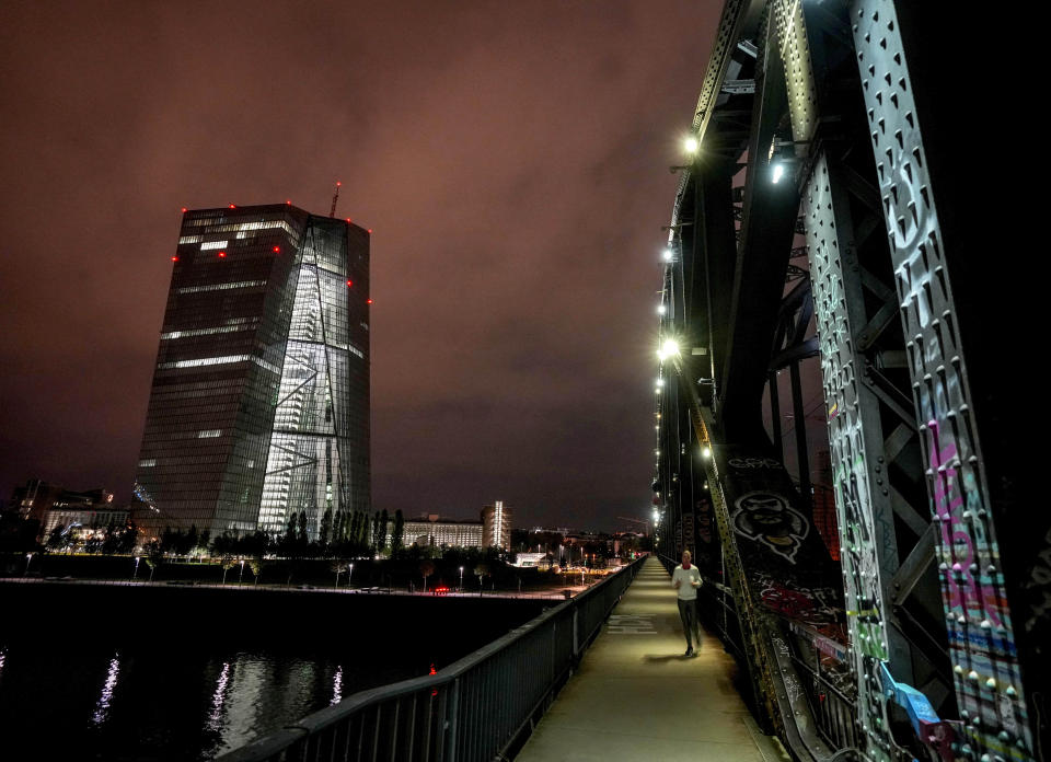 FILE - In this Monday, Sept. 20, 2021 file photo, a woman runs across a bridge with the European Central Bank in background in Frankfurt, Germany. The European Central Bank's first climate stress test, published Wednesday Sept. 22, 2021, shows high risks for of loan defaults for banks in fire-plagued southern Europe and argues that an earlier and orderly shift to greener energy will have costs that hit manufacturing, mining and electric utilities _ but pay off for the economy over the long run. (AP Photo/Michael Probst, File)
