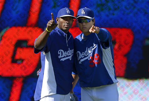Los Angeles Dodgers' Yasiel Puig, left, and Ryu Hyun-Jin, of South Korea, gesture toward a camera during batting practice prior to the Dodgers' baseball game against the San Francisco Giants, Tuesday, June 25, 2013, in Los Angeles. (AP Photo/Mark J. Terrill)