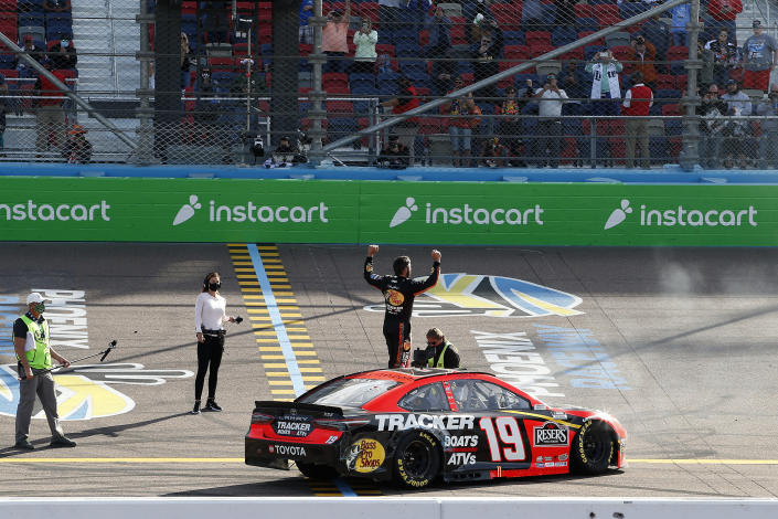 Martin Truex Jr. stands on his car as he celebrates after winning a NASCAR Cup Series auto race at Phoenix Raceway, Sunday, March 14, 2021, in Avondale, Ariz. (AP Photo/Ralph Freso)