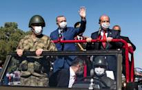 Turkish President Recep Tayyip Erdogan (C-L) and Turkish Cypriot leader Ersin Tatar (C-R) wave as they take part in a parade in the northern part of Cyprus' divided capital Nicosia