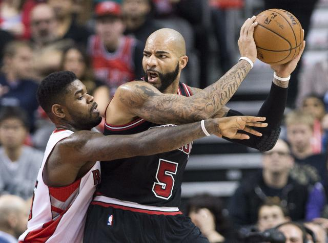 Toronto Raptors forward Amir Johnson, left, guards against Chicago Bulls forward Carlos Boozer, right, during first-half NBA basketball game action in Toronto, Friday, Nov. 15, 2013. (AP Photo/The Canadian Press, Nathan Denette)