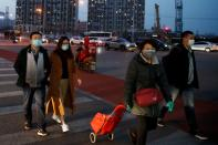 People wear face masks outside a shopping mall in Beijing as the country is hit by an outbreak of the novel coronavirus