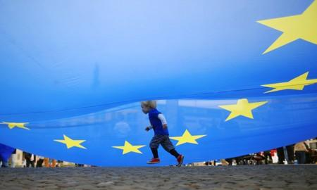 """A child runs under an EU flag during a rally under the slogan """"Stop the Coup"""" to protest against attempts to force through a no-deal Brexit, in Berlin"""