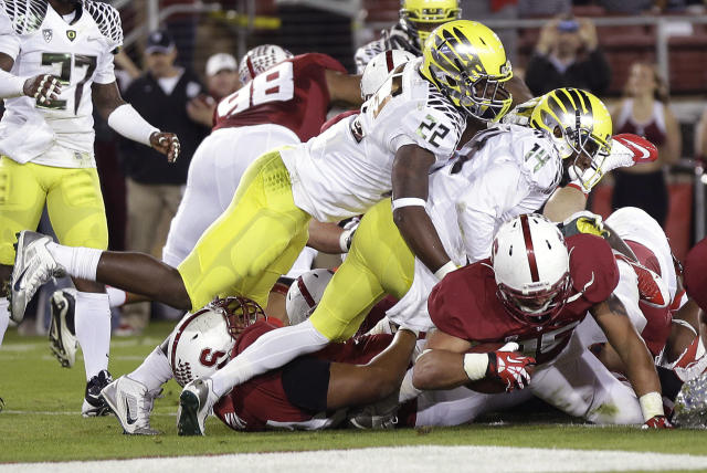 Stanford running back Tyler Gaffney, bottom right, scores on a 2-yard touchdown under Oregon linebacker Derrick Malone (22) and cornerback Ifo Ekpre-Olomu (14) during the first quarter of an NCAA college football game in Stanford, Calif., Thursday, Nov. 7, 2013. (AP Photo/Marcio Jose Sanchez)