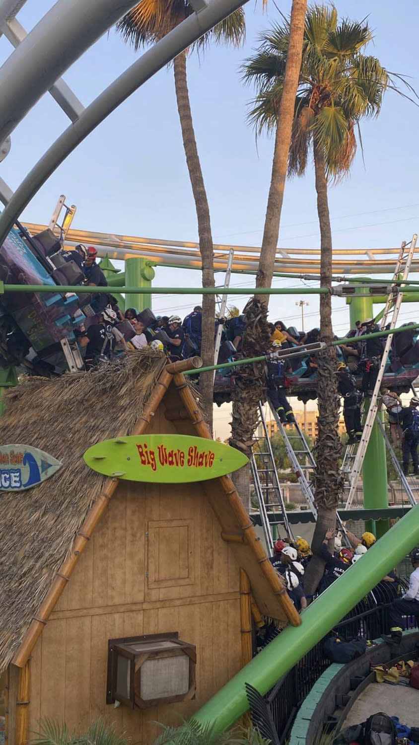 This photo provided by Phoenix Fire Department shows responders rescuing people stuck on a roller coaster at Castles N' Coasters on Saturday, May 15, 2021 in Phoenix. The Phoenix Fire Department said the ride got stuck Saturday, with riders perched 20 feet (six meters) off the ground. Rescue crews were dispatched and were able to escort 22 people off the ride safely. (Phoenix Fire Department via AP)