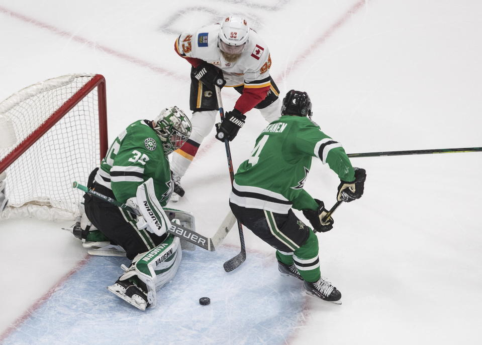 Calgary Flames' Sam Bennett (93) is stopped by Dallas Stars' goalie Anton Khudobin (35) as Miro Heiskanen (4) defends during second period NHL Western Conference Stanley Cup playoff hockey action in Edmonton, Alberta, Tuesday, Aug. 18, 2020. (Jason Franson/The Canadian Press via AP)