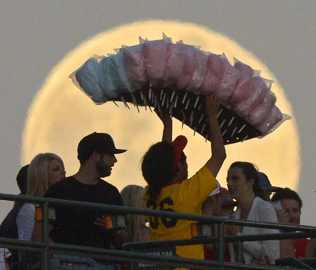 FILE - In this June 22, 2013 file photo, a cotton candy vendor walks in front of a full moon during the Los Angeles Angels' baseball game against the Pittsburgh Pirates, in Anaheim, Calif. The photo was part of a series of images by photographer Mark J. Terrill which won the Thomas V. diLustro best portfolio award for 2013 given out by the Associated Press Sports Editors during their annual winter meeting in Indianapolis. (AP Photo/Mark J. Terrill, File)