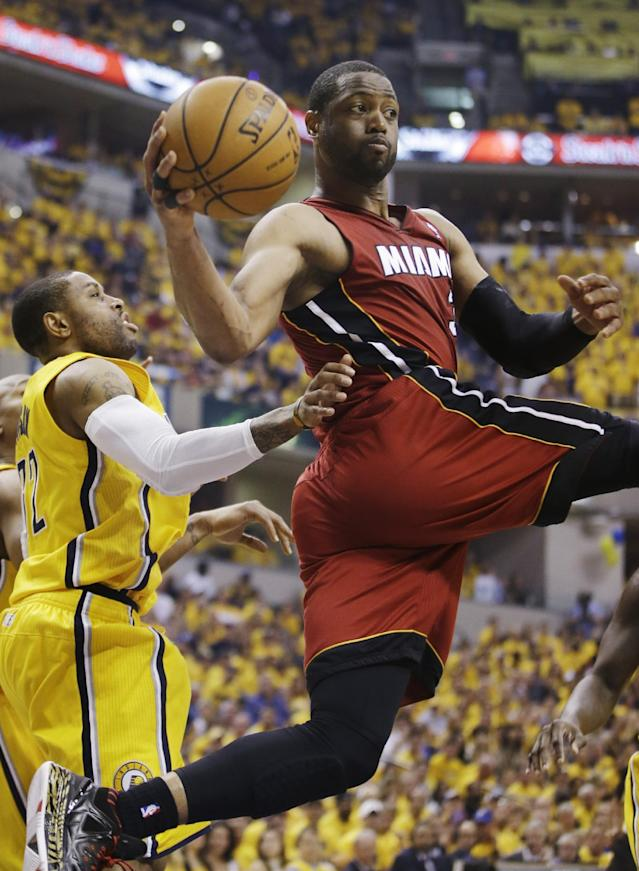Miami Heat guard Dwyane Wade (3) looks to pass as Indiana Pacers guard C.J. Watson (32) defends during the first half of Game 1 of the Eastern Conference finals NBA basketball playoff series Sunday, May 18, 2014, in Indianapolis. (AP Photo/Darron Cummings)