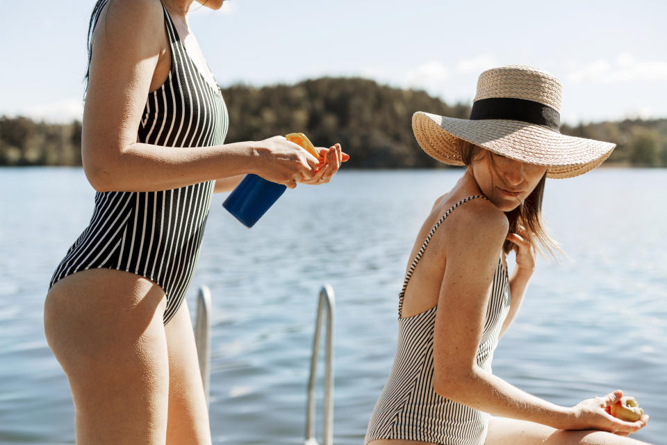 Two women wearing black and white swimsuits on a jetty at a lake. One woman applies sunscreen to the other woman's back