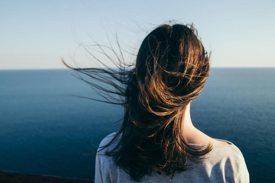 Woman with dark hair stands on a top cliff over blue sea view while wind.