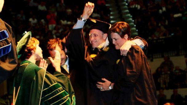 PHOTO: Sam Bridgman stood up with the help of two friends and physical trainers to walk across the graduation stage at USF, May 7, 2017. (Keith Morelli/USF Muma College of Business)