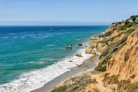 """<p><strong>Give us the wide-angle view: what kind of beach are we talking about?</strong><br> El Matador is the kind of beach an Angeleno immediately takes you to from the airport. It's a natural beauty—hidden away down a steep staircase with dramatic craggy rock formations that seem to have risen from the Pacific, plus tide pools that offer a glimpse at our undersea friends. It's not a huge beach, but it's big enough to find a spot underneath the cliffs, and the rocks have archways and holes you can crawl through during low tide—like a jungle gyms for adults.</p> <p><strong>How accessible is it?</strong><br> There's a tiny free parking lot, but on the weekends you'll probably have to park on the side of the <a href=""""https://www.cntraveler.com/story/the-most-california-road-trip-ever-pacific-coast-santa-monica-san-simeon?mbid=synd_yahoo_rss"""" rel=""""nofollow noopener"""" target=""""_blank"""" data-ylk=""""slk:Pacific Coast Highway"""" class=""""link rapid-noclick-resp"""">Pacific Coast Highway</a> and walk over. To get to the beach, there's a dirt path that leads to a staircase—both of these are steep, so it's inaccessible to those with mobility issues.</p> <p><strong>Decent services and facilities, would you say?</strong><br> There are zero services or amenities at El Matador. It's a natural wonder. Bring your own beach towels, sunscreen, and picnic gear, and you'll be all set for the day.</p> <p><strong>How's the actual beach stuff—sand and surf?</strong><br> The rocks in the water by the caves make most of El Matador a no-swim zone, though there are parts where you can swim. It's a popular spot for snorkelers, but it's mainly for strolls, sunbathing, and sunset views.</p> <p><strong>Can we go barefoot?</strong><br> The smooth sands make El Matador an easy walking beach. Strip off your sneakers and your socks and let the firm, cool sand sift through your toes.</p> <p><strong>Anything special we should look for?</strong><br> Head to El Matador during low tide. That way you can grab the dr"""