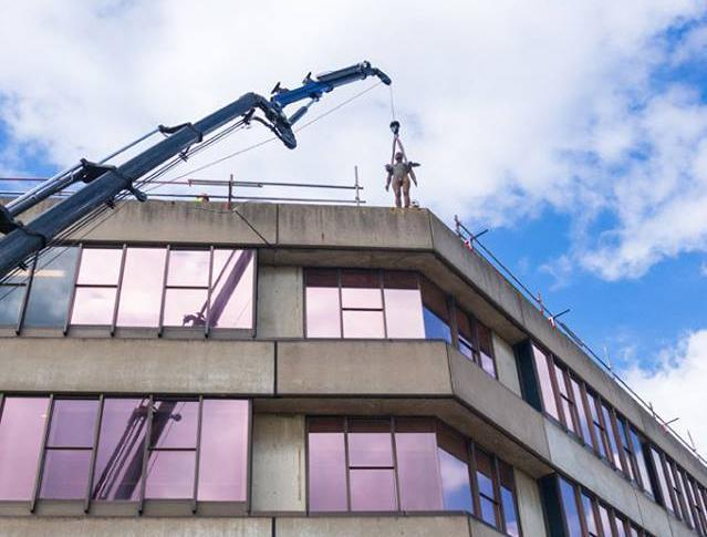 An Antony Gormley sculpture from the series 'Another Place' is lifted onto a roof at UEA: Facebook/ Sainsbury Centre for Visual Art