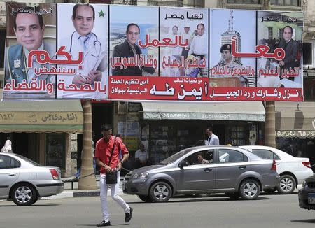 Vehicles are stuck in a traffic jam near an election campaign billboard of presidential candidate and former army chief Abdel Fattah al-Sisi near Tahrir Square in Cairo