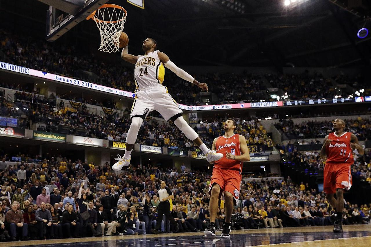 Indiana Pacers forward Paul George (24) dunks infront of the Los Angeles Clippers Hedo Turkoglu (8) and Jamal Crawford (11) during the second half of an NBA basketball game in Indianapolis, Saturday, Jan. 18, 2014. The Pacers won 106-92. (AP Photo/AJ Mast)