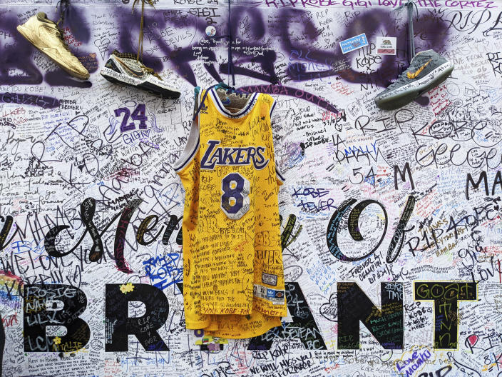 FILE - In this Feb. 2, 2020, file photo, sneakers and a Los Angeles Lakers uniform with the numbers worn by NBA star Kobe Bryant are left at a memorial for Bryant while fans gather to pay their respect near Staples Center in Los Angeles. Bryant, the 18-time NBA All-Star who won five championships and became one of the greatest basketball players of his generation during a 20-year career with the Lakers, died in a helicopter crash Sunday, Jan. 26. (AP Photo/Damian Dovarganes, File)