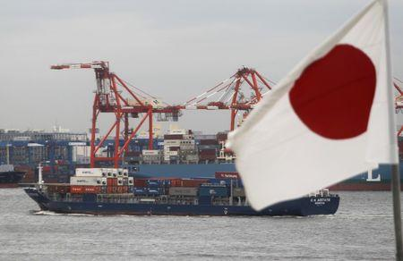 A Japanese flag is seen in front of a cargo ship carrying containers at a port in Tokyo