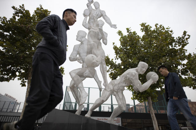 "In this Friday, Oct. 11, 2019, photo, Chinese men walk by a sculpture depicting basketball players in Beijing. When Houston Rocket's general manager Daryl Morey tweeted last week in support of anti-government protests in Hong Kong, everything changed for NBA fans in China. A new chant flooded Chinese sports forums: ""I can live without basketball, but I can't live without my motherland.""(AP Photo/Ng Han Guan)"