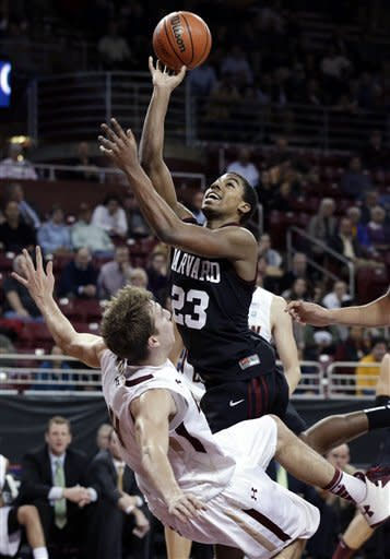 Harvard forward Wesley Saunders (23) drives into Boston College forward Eddie Odio (4) as he shoots during the first half of an college basketball game in Boston, Tuesday, Dec. 4, 2012. (AP Photo/Elise Amendola)