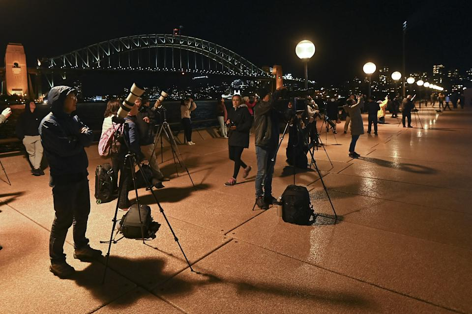 SYDNEY, AUSTRALIA - MAY 26: The Sydney Harbour Bridge can be seen as photographers, astronomers and star gazers observe the full moon, known as a âsuper flower blood moonâ, seen during its total lunar eclipse phase, in Sydney, Australia, on May 26, 2021. The full moon on Wednesday will be the year's biggest âsuper moonâ and feature the first total lunar eclipse in more than two years, known as a âsuper blood moonâ. A âsuper blood moonâ is when a total lunar eclipse (or âblood moonâ) happens at the same time as a âsuper moonâ, when the moon will be at perigee, or the closest point to Earth in its orbit, making it appear about 7% larger than normal and 15% brighter. The eclipse will be visible from Australia, New Zealand, the Pacific, South-East Asia and parts of North and South America at the same time. (Photo by Steven Saphore/Anadolu Agency via Getty Images)