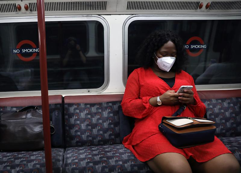 A commuter wearing a protective face mask while traveling on a Victoria line underground train in London, as face coverings becomes compulsory on public transport in England Picture date: Friday July 3, 2020.