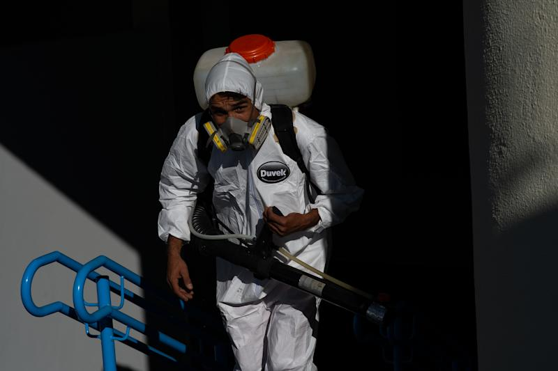 BRASILIA, BRAZIL - JULY 31: A sanitation worker wearing PPE disinfects the stairs of a public school amidst the coronavirus (COVID-19) pandemic at the Candangolância on July 21, 2020 in Brasilia. The government of the capital of Brazil intends to return to face-to-face classes in August as the country reports over 2.610,000 confirmed positive cases of Coronavirus and reports over 91,263 deaths. (Photo by Andressa Anholete/Getty Images)