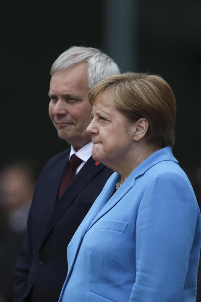 German Chancellor Angela Merkel, right, and Prime Minister of Finland Antti Rinne listen to the national anthems at the chancellery in Berlin, Wednesday, July 10, 2019. Merkel's body shook visibly as she stood alongside the Finnish prime minister and listen to the national anthems during the welcoming ceremony at the chancellery. (AP Photo/Markus Schreiber)
