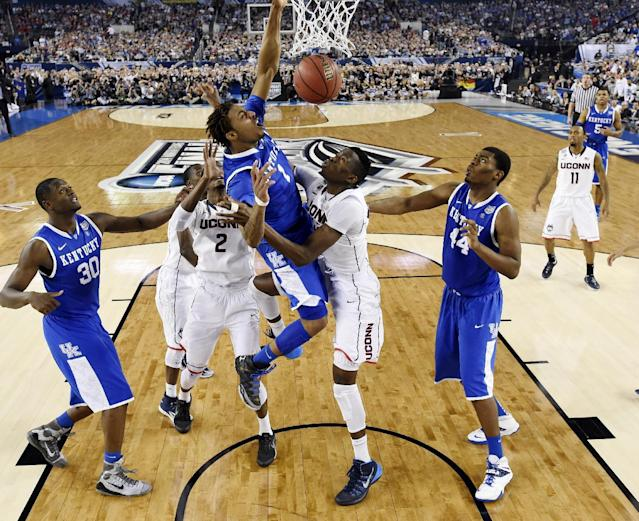 Kentucky guard James Young (1) dunks between Connecticut forward DeAndre Daniels (2) and center Amida Brimah (35) during the second half of the NCAA Final Four tournament college basketball championship game Monday, April 7, 2014, in Arlington, Texas. (AP Photo/Chris Steppig, pool)