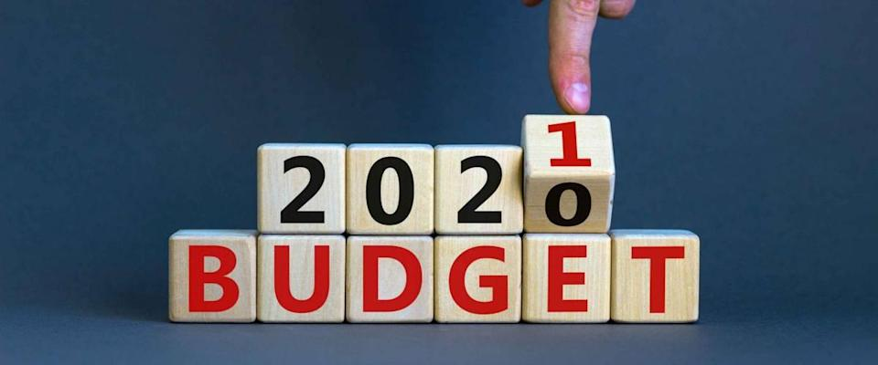 Business concept of planning 2021. Male hand flips wooden cube and change the inscription 'BUDGET 2020' to 'BUDGET 2021'. Beautiful grey background, copy space.