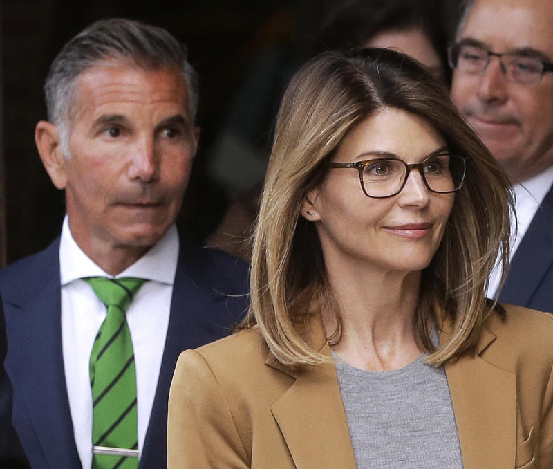 FILE - In this April 3, 2019, file photo, actress Lori Loughlin, front, and husband, clothing designer Mossimo Giannulli, left, leave federal court in Boston after facing charges in a nationwide college admissions bribery scandal. Loughlin and Giannulli are scheduled for a hearing in the bribery scam case on Tuesday, Aug. 27 in Boston. (AP Photo/Steven Senne, File)